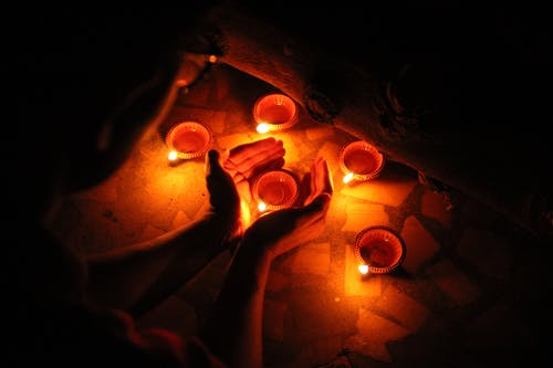 Faceless person burning candles in darkness