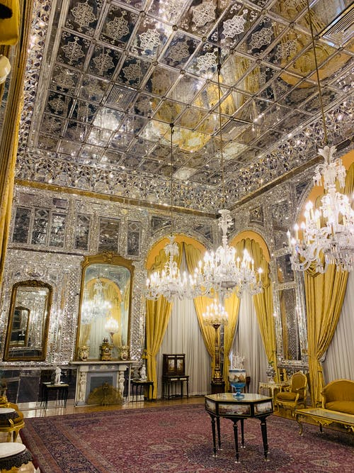 Interior design of spacious luxurious room of imperial palace with massive cut glass chandeliers carpet and classic furniture reflecting in mirror walls and ceiling