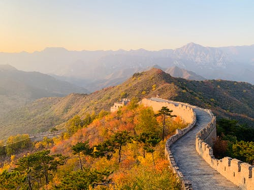 Picturesque landscape of Great Wall of China on hill with green trees and mountains on background on sunny day