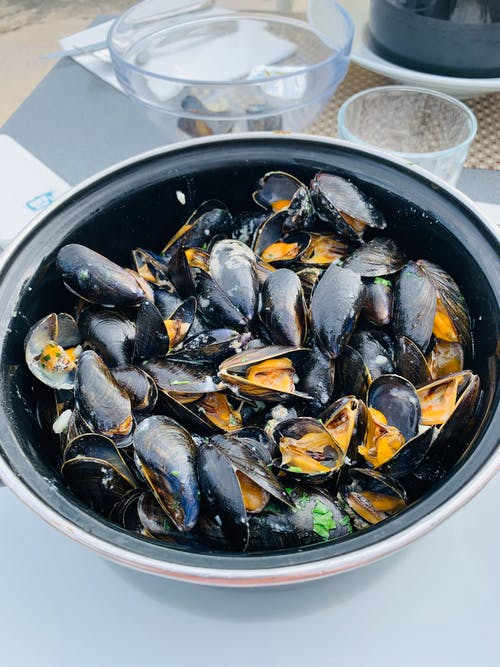 Big bowl with mussels on table