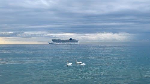 Ship floating in sea against cloudy sky