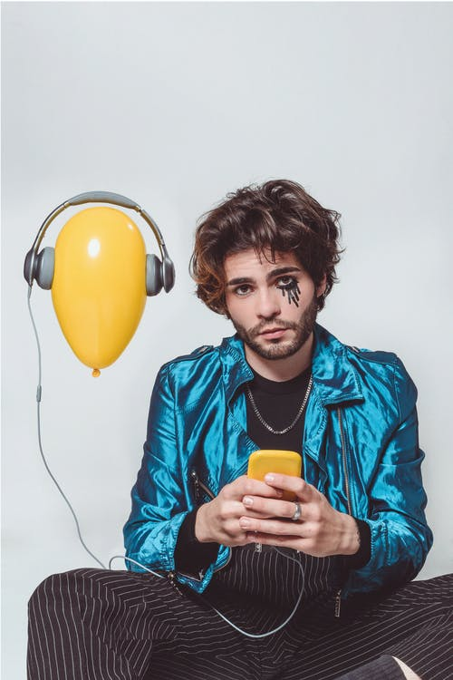 Stylish sad man playing songs on smartphone for air balloon