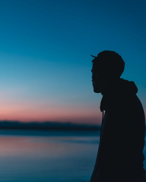 Silhouette of man standing on shore at sunset