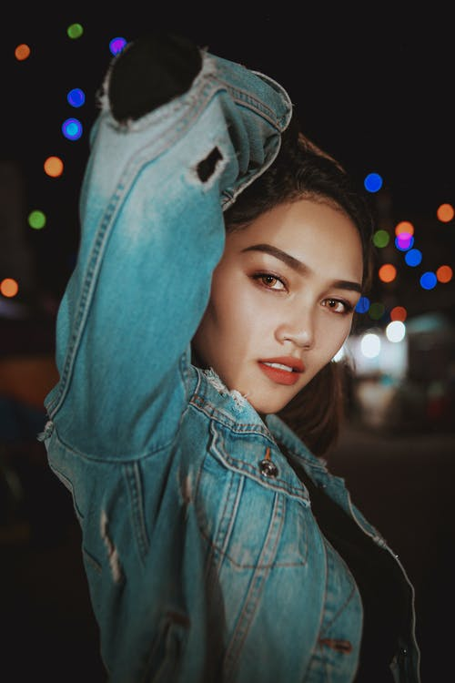 Young woman in denim jacket on illuminated street