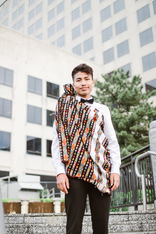 Low angle of positive Asian guy wearing suit and scarf smiling and looking at camera
