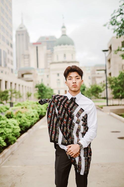 Confident ethnic stylish man in modern city
