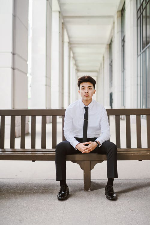 Well dressed Asian man sitting on wooden bench