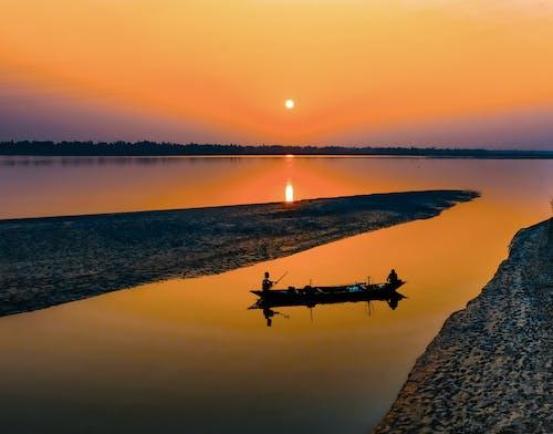 Fishermen in boat in calm river