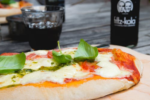 Pizza Top With Green Leafy Vegetable Near Glass of Black Liquid