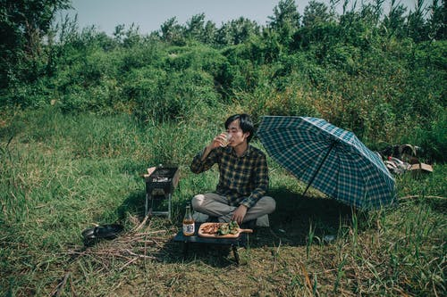 Photo of Man Drinking While Sitting on Grass Field