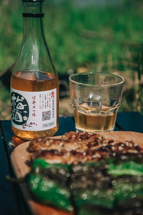 Photo of Brown Alcoholic Beverage Near Wooden Plate
