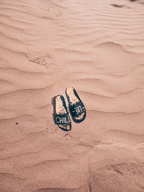 Black Slippers on Brown Sand
