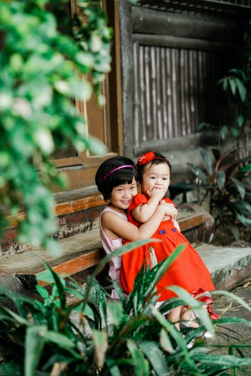 Photo of Girl Carrying Her Sister