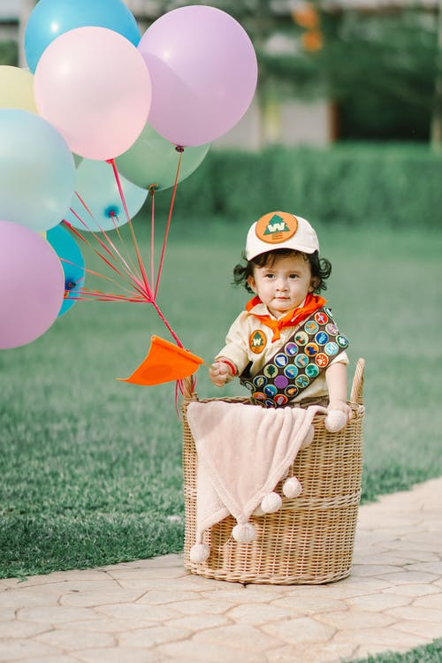Photo of Baby Standing Near Wicker Basket and Colorful Balloons