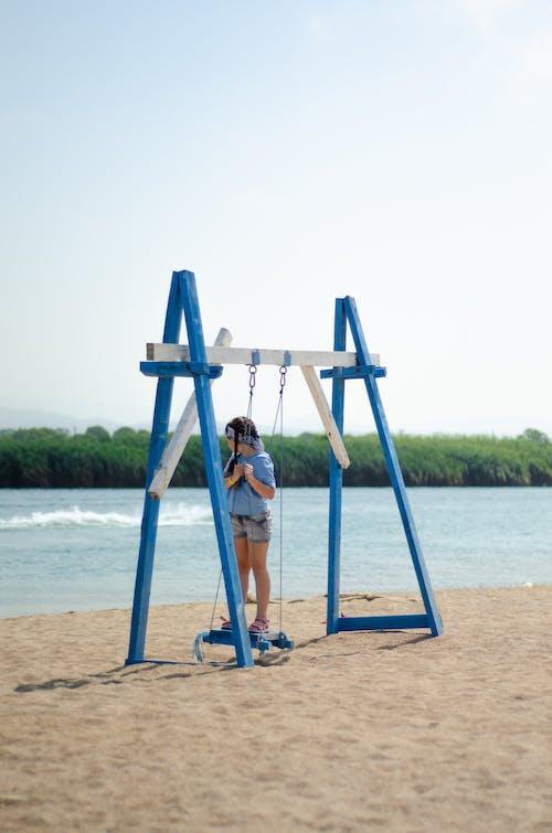 Girl Standing on Blue Swing
