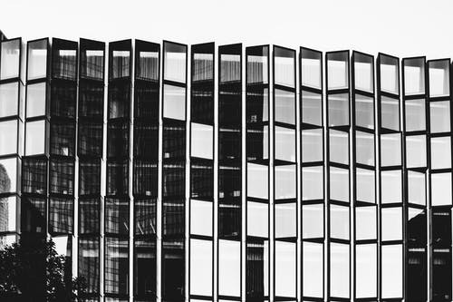 Black and white of high contemporary multi storey office construction with same transparent windows