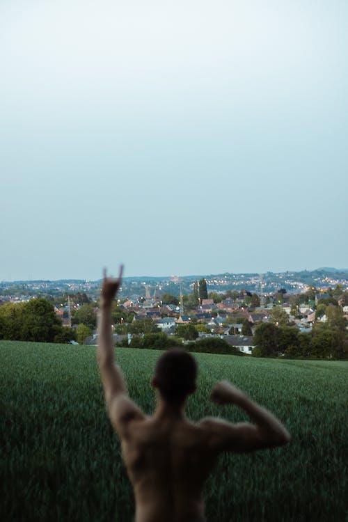 Shirtless man demonstrating rock n roll gesture
