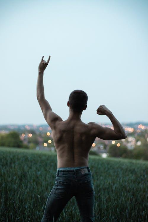 Man in Denim Jeans Standing on Green Grass Field