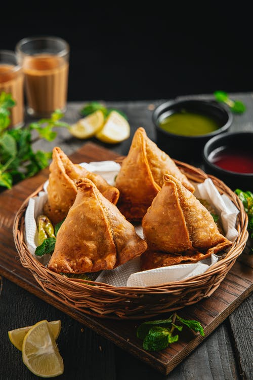 Fried golden samosas on white tissues in wicker basket on board surrounded by lemon and salad dressing in deep dishes and beverages in glass