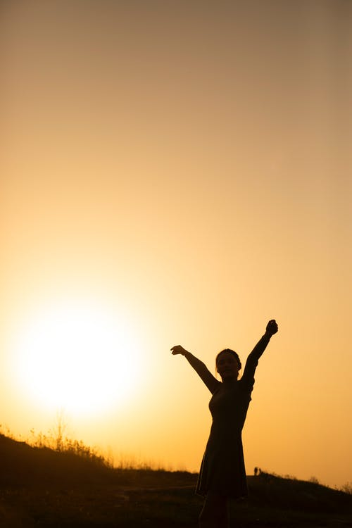 Silhouette of Man Raising His Hands during Sunset