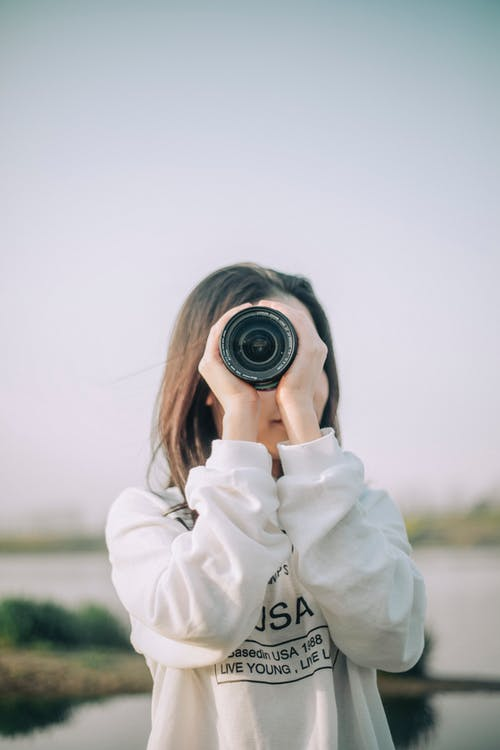 Woman in White Coat Holding Black Camera