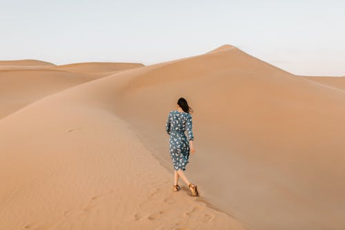 Woman in Floral Dress Walking on Desert