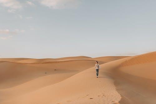 Photo of Man Walking on Desert