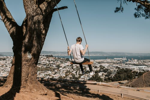 Photo of Man Wearing White Shirt While Sitting on Swing