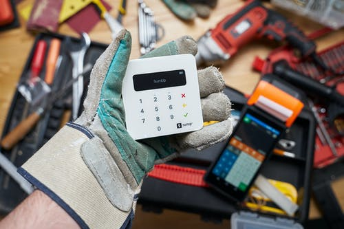 Faceless person in gloves showing modern cash register