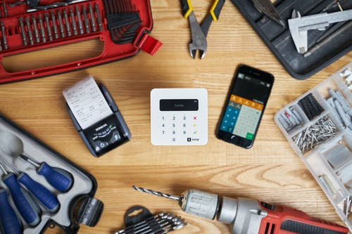 Modern cash registers and calculator on screen of smartphone among drill and pliers composing with other instrument for fixing and building