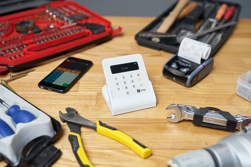 Red and black toolboxes next to smartphone and modern cash registers composing with pliers and wrenches on beige wooden table in bright room