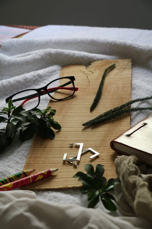 Eyeglasses and accessories on piece of carton in room