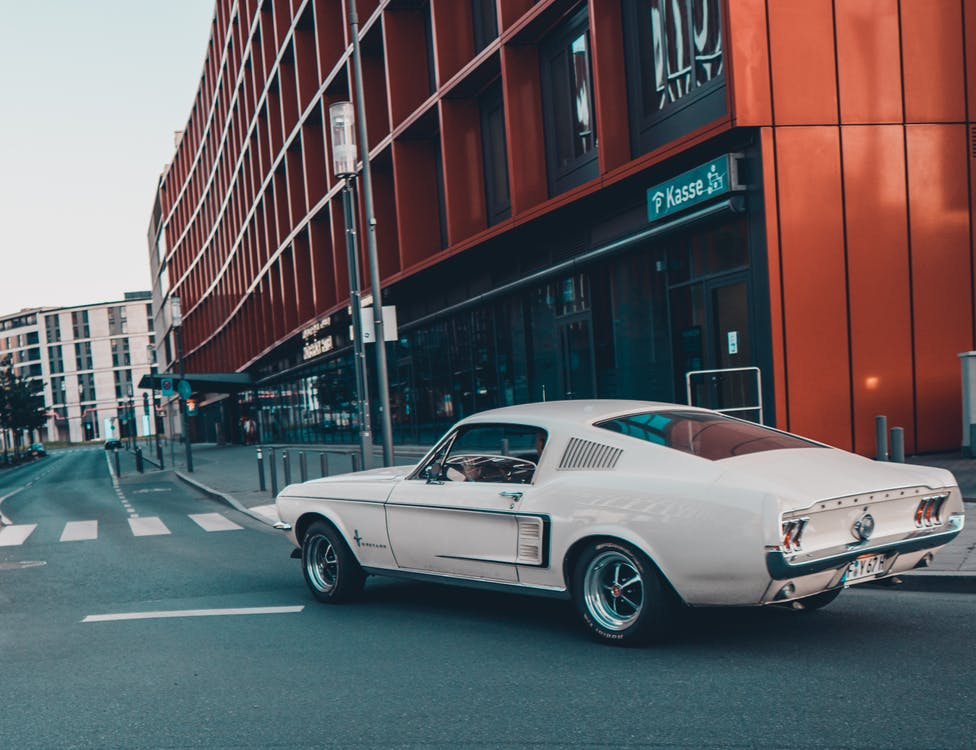 White Coupe on Road Near Red Building