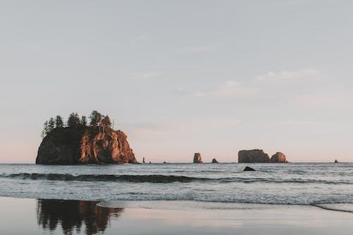 Gratis arkivbilde med bergformasjon, bølger, daggry
