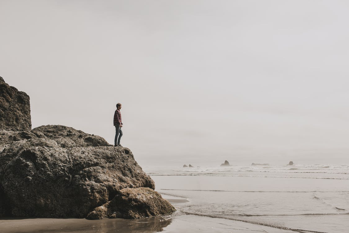 Photo of Man Standing on Rock Formation