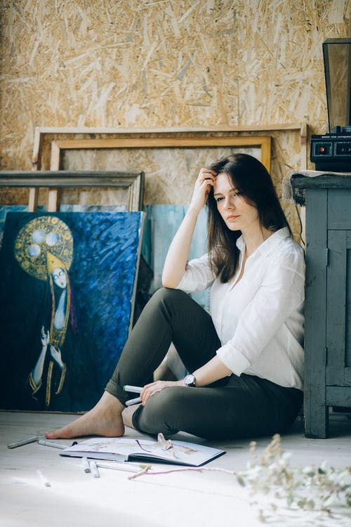 Photo of Woman Wearing White Long Sleeves and Black Pants While Sitting on Floor Looking Pensive