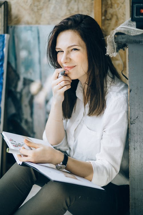 Woman in White Long Sleeve Shirt Holding White Book