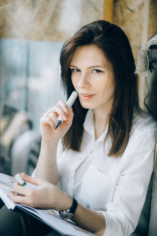 Woman in White Button Up Shirt Holding Marker