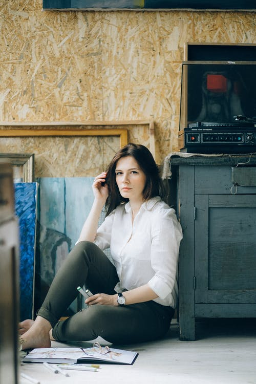 Woman in White Dress Shirt Sitting on Floor Near Wooden Cabinet
