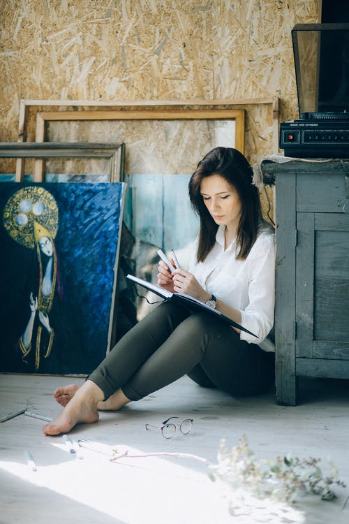Woman in White Long Sleeve Shirt and Black Pants Sitting Floor While Looking at a Book