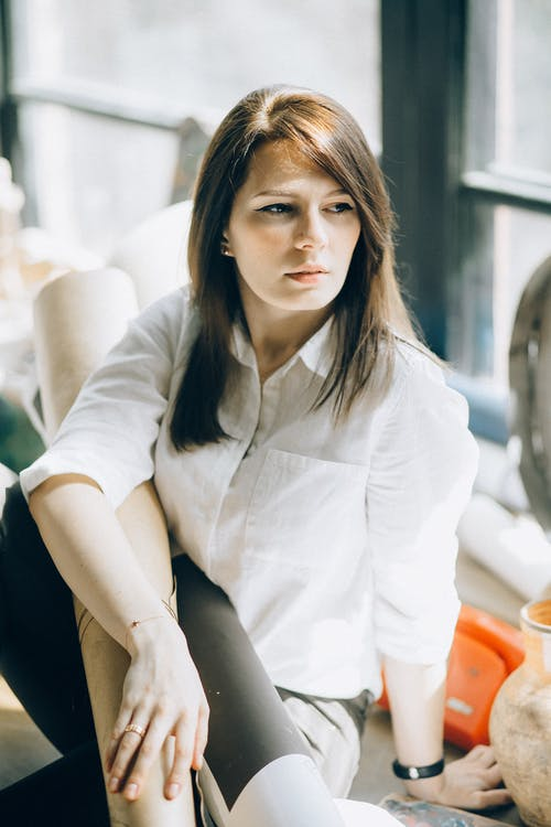 Woman in White Long Sleeve Shirt Looking Serious