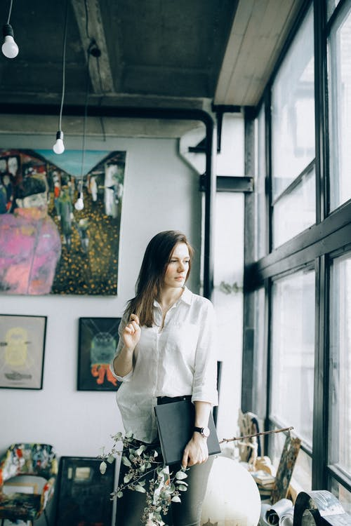 Woman in White Long Sleeve Shirt Standing Near Glass Window
