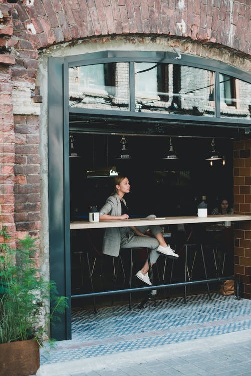 Stylish calm woman sitting at table in cafe