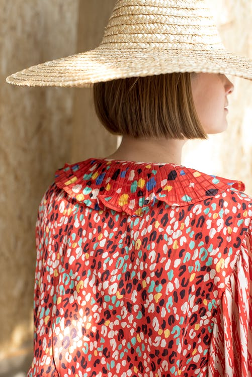 Back view unrecognizable stylish lady in colorful red summer dress and straw hat with short blond hair standing near beige wall and looking away