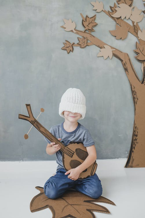 Full body smiling cute little boy in casual clothes with eyes covered with white knitted hat sitting on floor with toy dombra against gray wall and carton fake tree