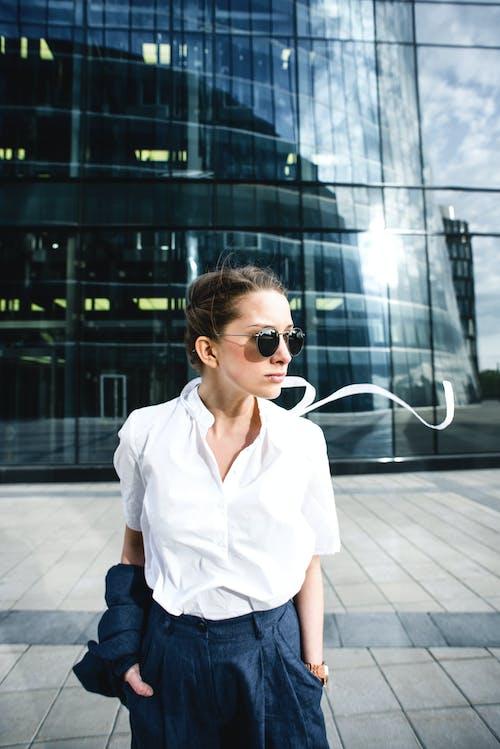 Confident businesswoman near modern glass building
