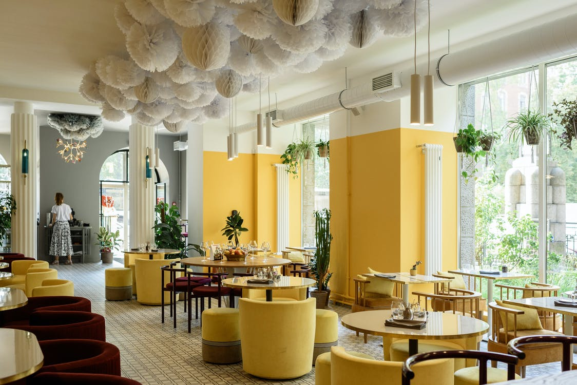 Creative interior design of modern spacious cafe with bright yellow walls and armchairs decorated with green plants and cozy lamps with big windows against lush greenery