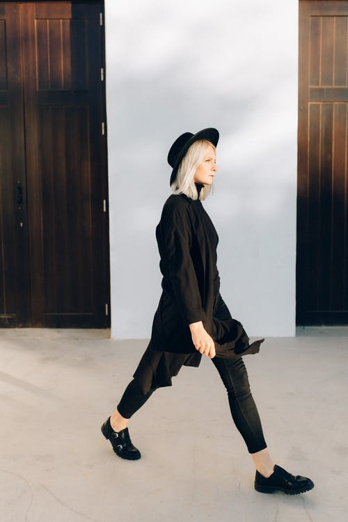 Woman in Black Coat and Black Hat While Walking