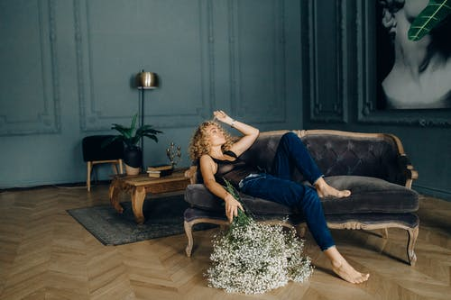 Photo of Woman Lying Down on Sofa While Holding White Flowers