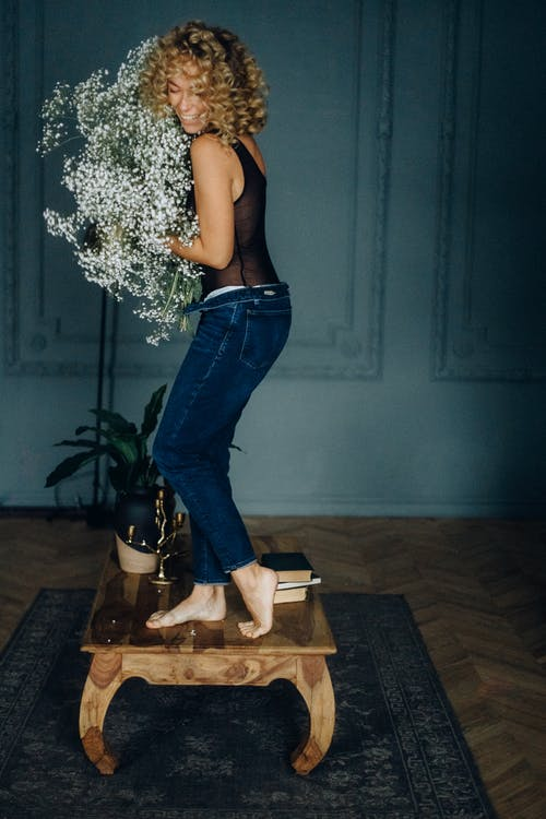 Photo of Woman Holding White Flowers While Standing on Wooden Table